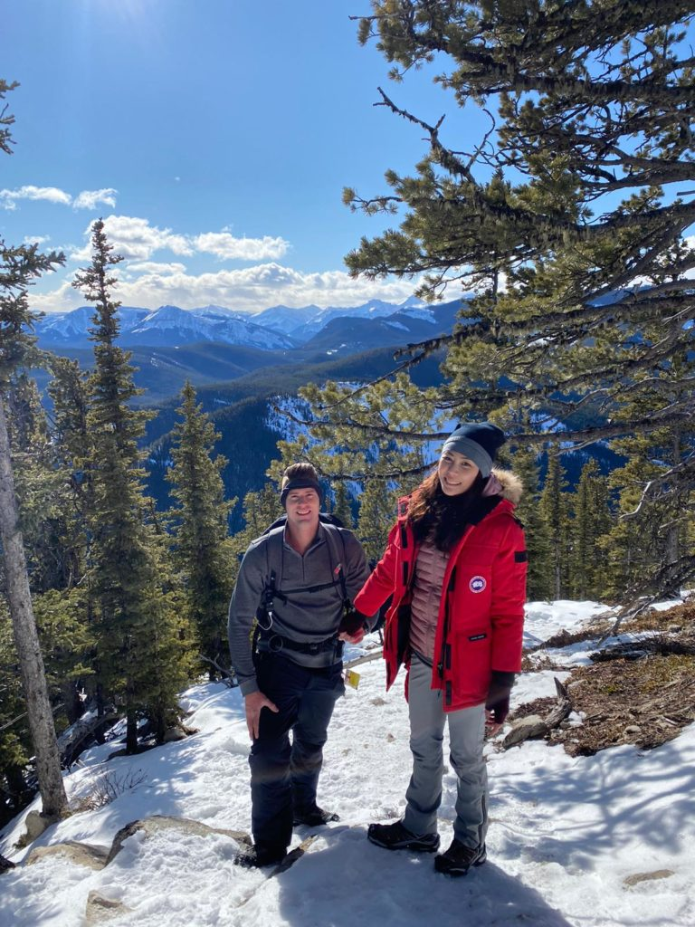 A picture of Stephen Wagner and Charlene Shang hiking with beautiful scenery behind.